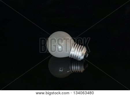 Turbid light bulb reflects from the dark surface