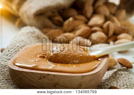 Homemade almond butter in a wooden bowl and a bag of jute.