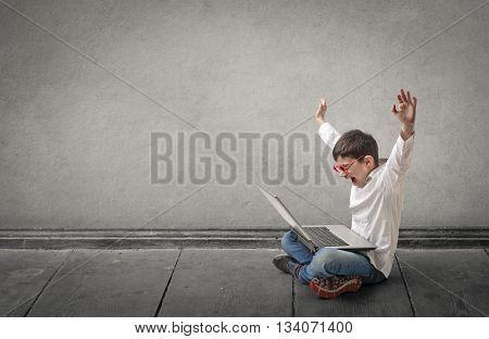 Happy boy using a laptop