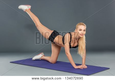 Fit athletic woman exercising in a studio down on the floor and one knee with the other leg raised up behind her in the air. look at the camera