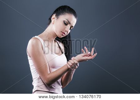 Body pain. Studio shot of beautiful young woman with dark brown hair. Woman suffering from wrist pain