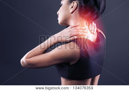 Body pain. Studio shot of beautiful young woman with dark brown hair. Woman suffering from neck ache. Red spot on neck