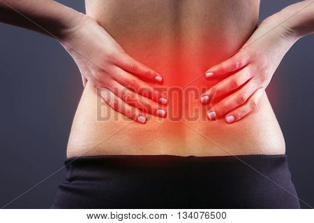 Body pain. Close up studio shot of woman. Woman suffering from backache. Red spot on back