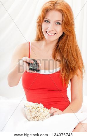 Young beautiful girl watching movie or tv in bed and eating  popcorn