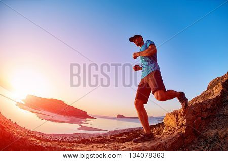 male hiker, traveler runs on the trail against sea and blue sky at the sunset. Balos beach on background, Crete, Greece