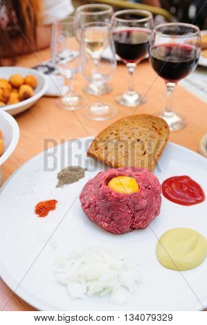 Beef tartare with fresh egg's yolk, mustard, pepper and roasted bread. Traditional Czech cuisine.