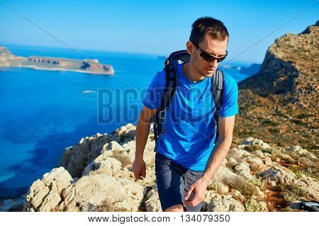 male traveler with backpack runs on the cliff against sea and blue sky at early morning. Balos beach on background, Crete, Greece