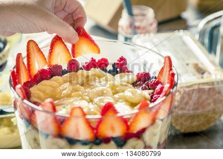 Closeup image of trifle being prepared in a glass bowl