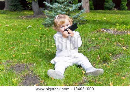 Cute baby girl with mobile phone sitting on green grass