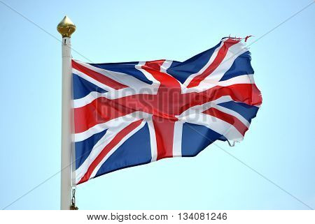 tattered union jack british flag on a windy day brexit