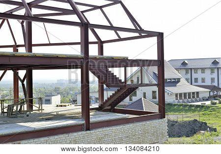 Metal frame building under white brick building