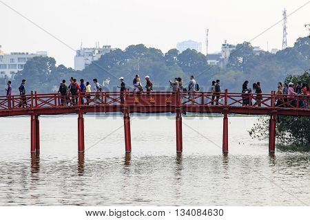 Hanoi Vietnam: February 21 2016: People walking on the Huc Bridge over the Hoan Kiem Lake