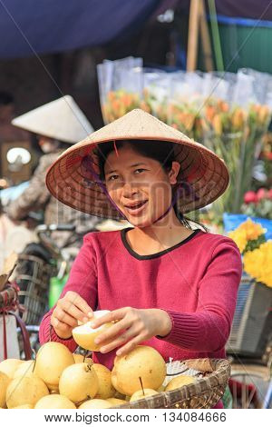 Hanoi Vietnam: February 21 2016: Womand selling fruits in a street market of Hoàn Kiếm the old quarter of Hanoi