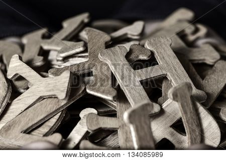 closeup of a pile of different wooden letters, in duotone