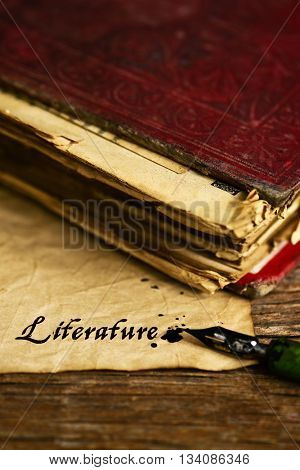 closeup of an old book, an old dip pen and a yellowish paper with the word literature written with black ink in it, on a rustic wooden table