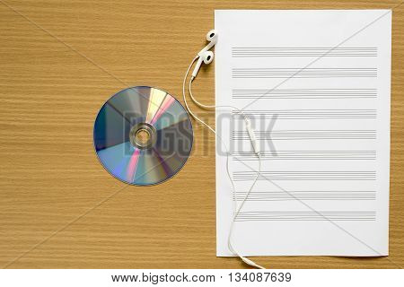 top view of music staff paper dvd dish and earphone on wood background