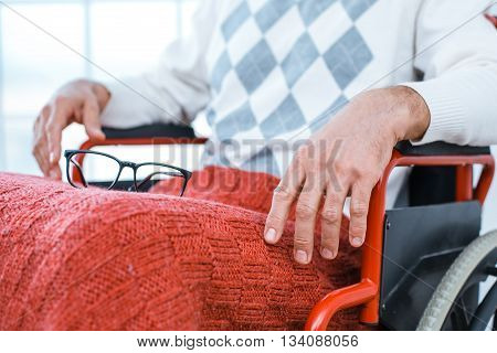 Adult man in wheelchair. Close up photo of man with glasses sitting in wheelchair