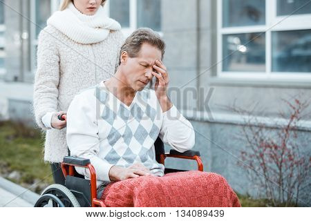 Adult man in wheelchair during walk. Nurse carrying sad patient on wheelchair. Man closing his eyes with hand