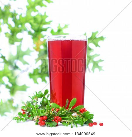 Red cold juice in big glass on white