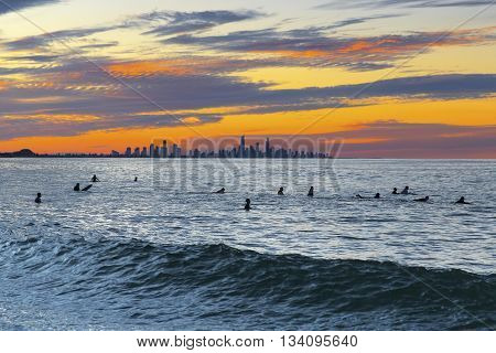 Colourful sunset over Surfers Pardise Gold Coast with surfer silhouettes in the ocean