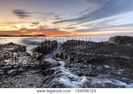 Currumbin Rock Gold Coast sunset with ocean tide coming in on Currumbin Rock