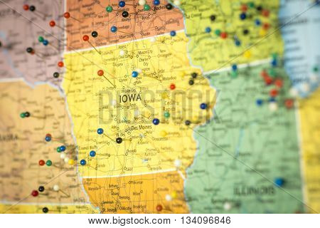Colorful detail map macro close up with push pins marking locations throughout the United States of America IA Iowa
