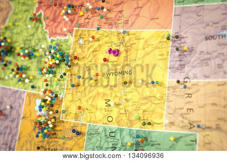 Colorful detail map macro close up with push pins marking locations throughout the United States of America WY Wyoming