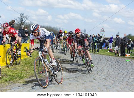 Hornaing France - April 10,2016: The peloton including the German cyclist Andre Greipel of Lotto-Soudal Team riding on a paved road in Hornaing France during Paris Roubaix on 10 April 2016.
