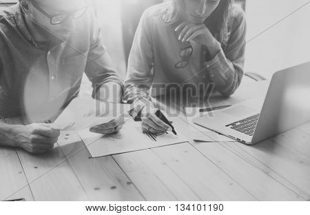 Account team discussion process.Photo business crew working with new startup project.Notebook on wood table. Idea presentation, analyze marketing plans.Creative process.Blurred background, black white