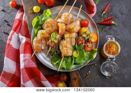 Raw chicken on wood skewers with tomatoes and lettuce. Top view