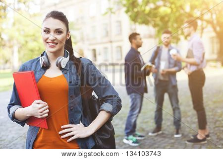 Enjoying university life. Portrait of attractive girl standing and holding a book. She is lookinh forward and smiling. Her friends are chatting on background