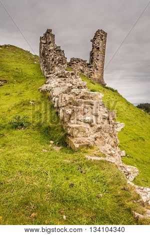 Remains of a wall at Harbottle Castle, a medieval site which is situated on a mound in the Coquetdale Valley Northumberland