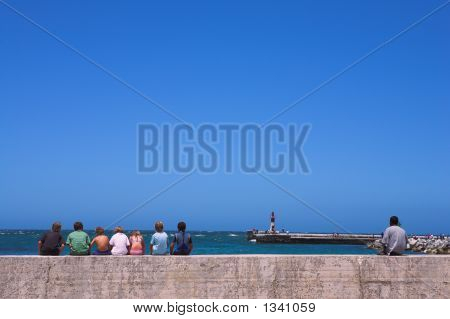 seven friends sitting together on the harbor breakwater wall poster