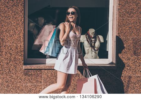 Beautiful shopaholic. Beautiful young woman carrying shopping bags and looking over shoulder with smile while walking along the street with fashion store in the background
