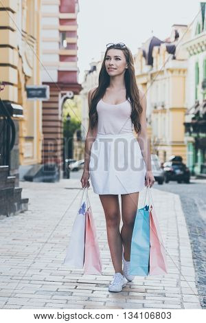 Enjoying day shopping. Full length of beautiful young smiling woman carrying shopping bags while walking along the street