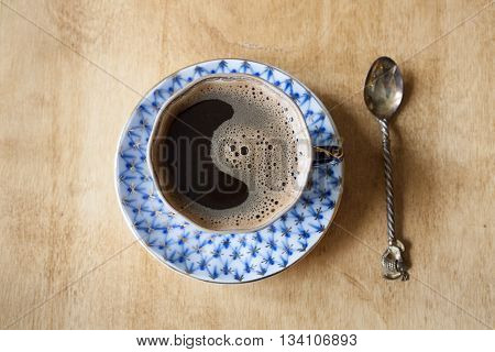 Black coffee with crema in an elegant cup and saucer with a blue pattern on a wooden table. Spoon with fish.