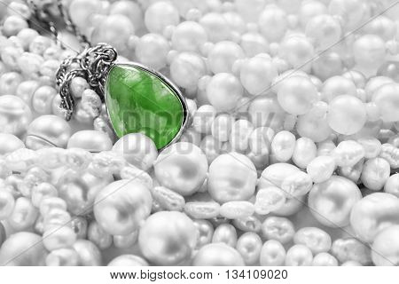 Green emerald pendant on white pearl as a background