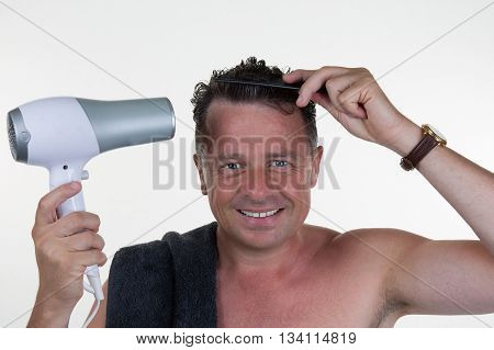 Attractive smiling man using blow dryer and comb in bathroom