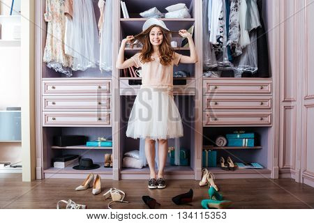 Young pensive beautiful girl choosing shoes in her wardrobe