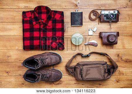 Travel concept boots, shirt, camera, lighter, flask, bag, penknife on the desk