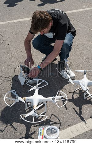 Saint-Petersburg Russia - June 4 2016: A young man sets up drone before the flight in a special area designed for training. Summer sunny day.