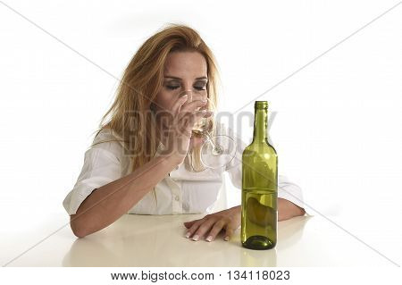 caucasian blond wasted and depressed alcoholic woman drinking white wine glass looking desperate and sad isolated on white in alcohol abuse and addiction and drunk housewife alcoholism problem