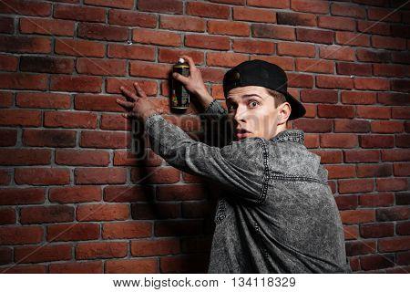 Graffiti man in shirt spraying red brick wall by aerosol can