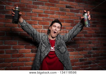 Graffiti man in cap getting ready to spray brick wall by aerosol can