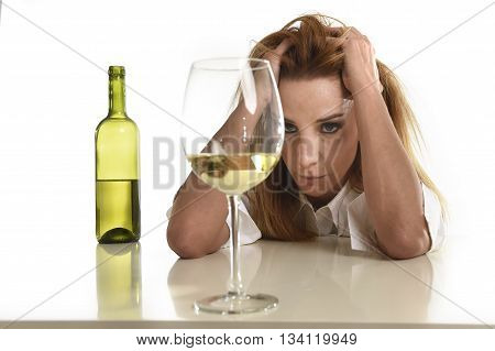 caucasian blond wasted and depressed alcoholic woman drinking white wine glass looking desperate and sad isolated on white in alcohol abuse and addiction and housewife alcoholism problem