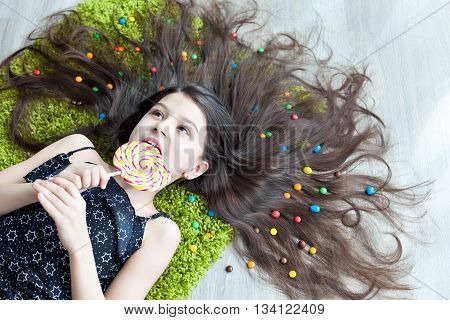 Little girl with dark hair lying on the floor among the sweets with his eyes closed and holding a large ledinets. View from above. Many candies in her hair. Happy smiling