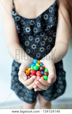 Portrait of a little girl with dark long hair holding a large handful of colorful candies. Happy smiling baby.