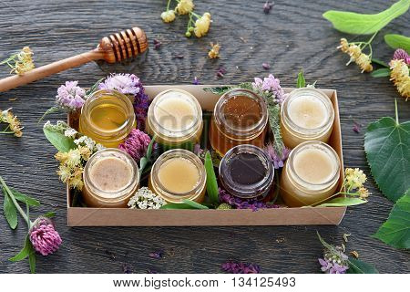 A box with eight different kinds of honey decorated with blossoms of bee plants.