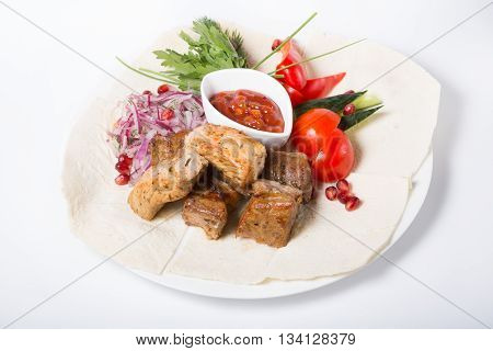 Roasted kebab meat served with sauce and vegetables