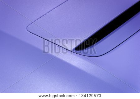 Fragment of sport car hood with air intake, vehicle steel bodywork, violet paint coating texture, abstract
